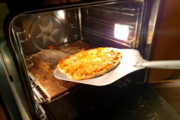 Pizza pieczona na kamieniu w piekarniku wyjmowana łopatą