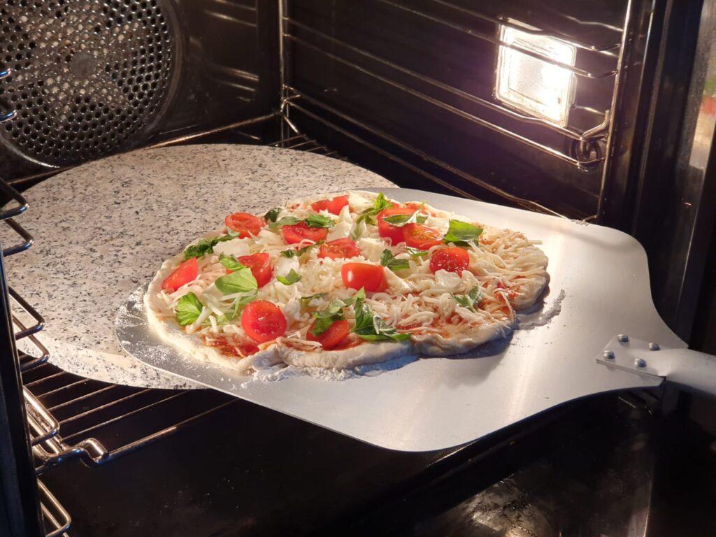 Pizza z pomidorami i bazylią wkładana do piekarnika z kamieniem granitowym