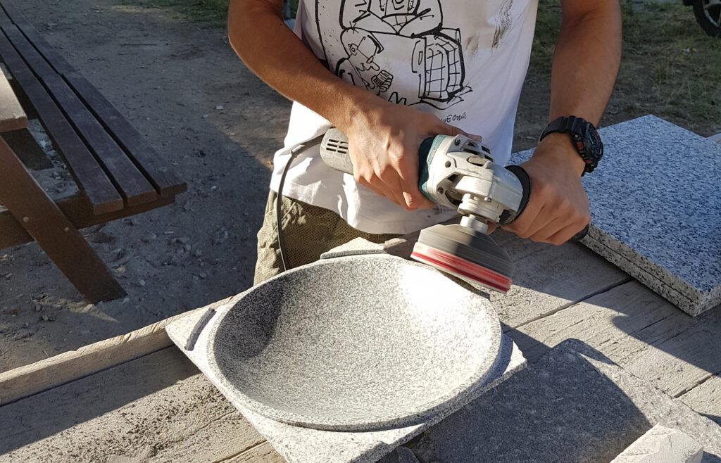 Kamieniarz ręcznie szlifujący misę z kamienia.