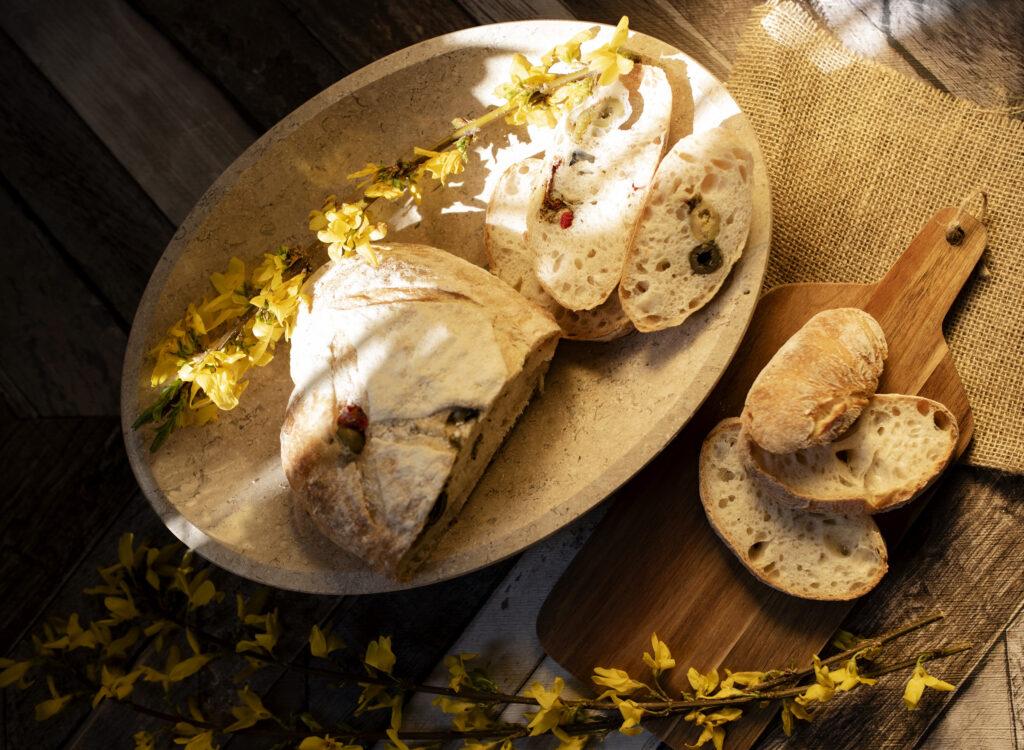 Kamienna owalna misa na niej na niej podany świeży pokrojony chleb.