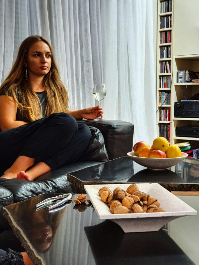 Kamienne patery z owocami i orzechami na kawowych stolikach, w tle kobieta na kanapie z kieliszkiem wina