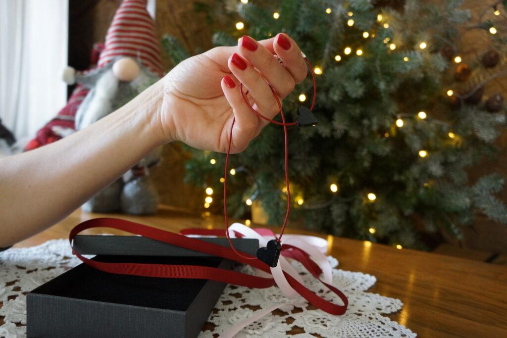 Serce na czerwonym rzemyku, biżuteria wyjmowan z pudełka. Widać tylko rękę kobiety z pomalowanymi na czerwono paznokciami, rozwiązane wstążki, w tle choinkowe światełka.
