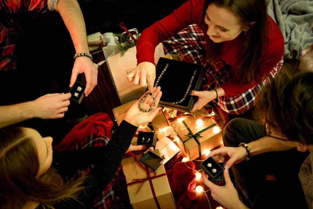 Świąteczny klimat, światełka, kokardki. Grupka przyjaciół ogląda  prezenty - damską biżuterię i spinki do koszuli z kamieniami naturalnymi. Niektóre prezenty jeszcze nie są otwarte.