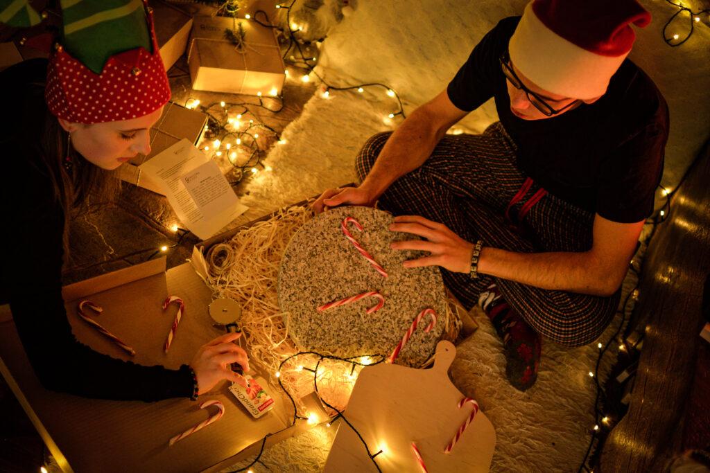 On i ona w świątecznych czapkach, wokół światełka, choinkowe cukierki. Rozpakowują wspólny prezent - okrągły kamień do pizzy, łopatka i nóż