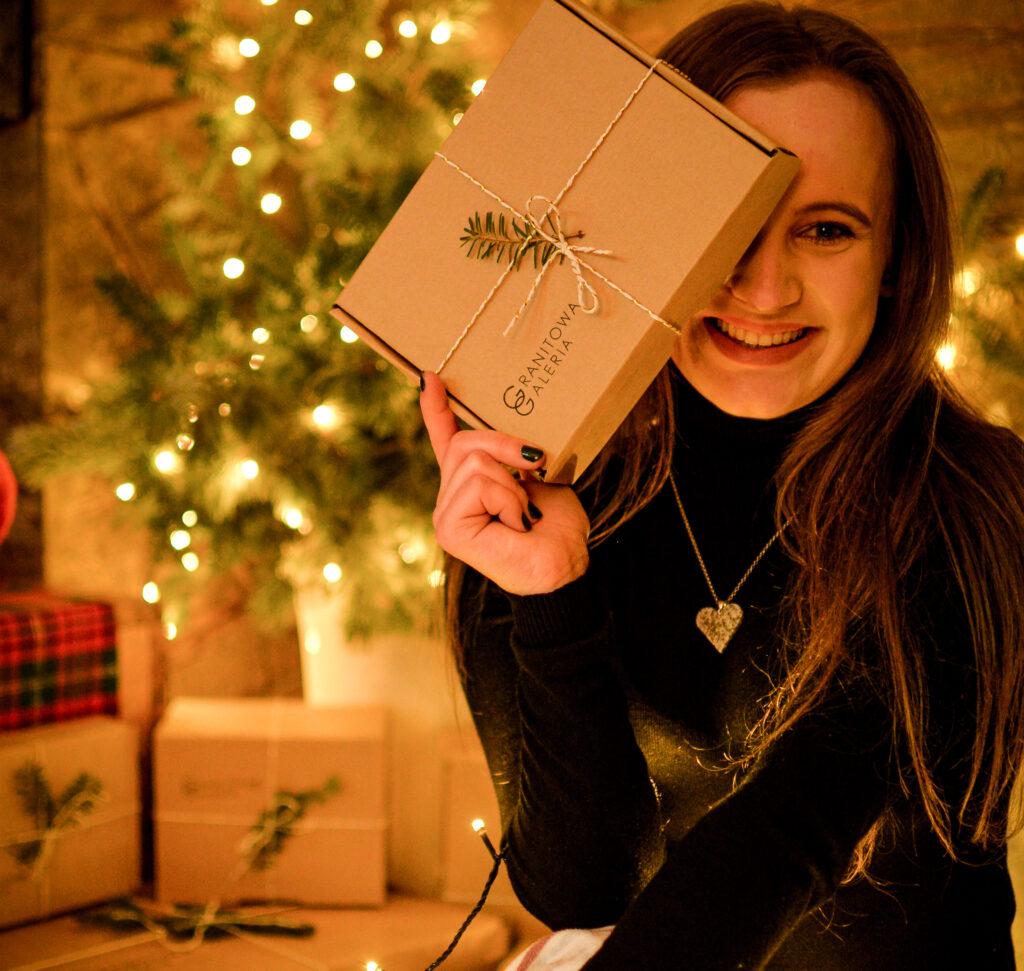 Uśmiechnięta dziewczyna w ręku prezent dla niej na święta, w tle choinkowe światełka, prezenty pod choinką